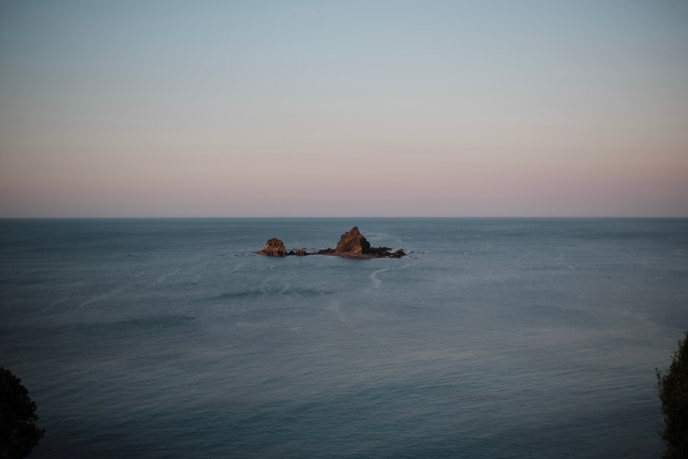 man and woman lying on brown rock in the middle of ocean during daytime