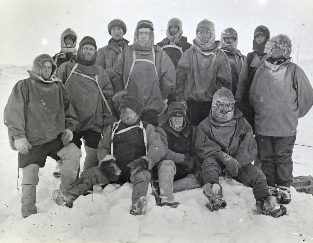 group of men in black coat on snow covered ground