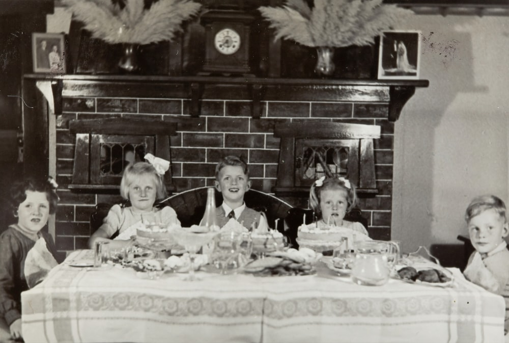 grayscale photo of family on table