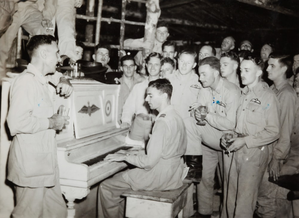 grayscale photo of 4 men standing beside piano