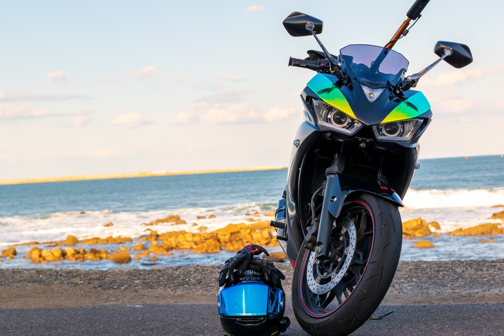 blue and black sports bike on gray sand near body of water during daytime