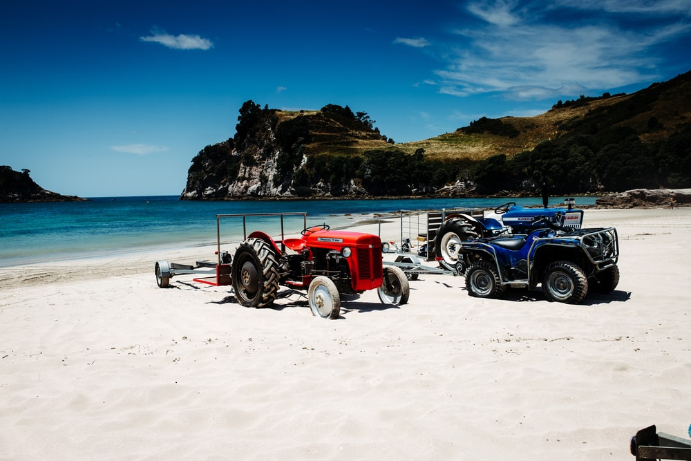 red tractor on beach during daytime