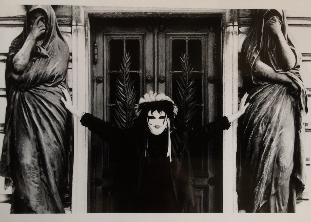 woman in black long sleeve shirt standing beside window