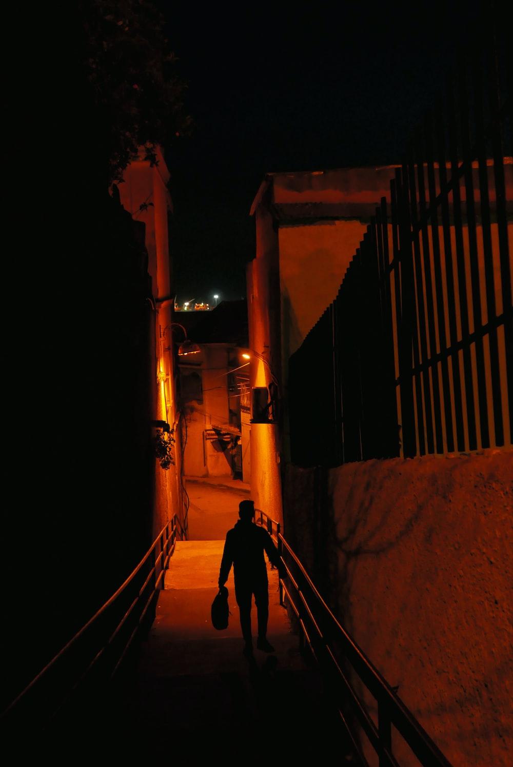 man in black jacket walking on pathway during night time