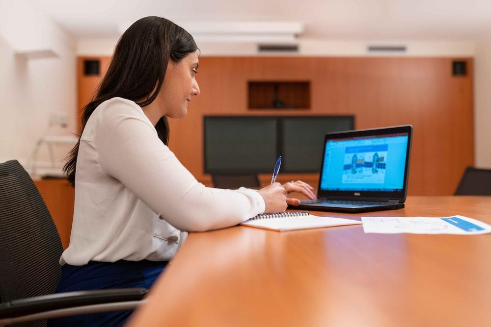 woman in white long sleeve shirt using black laptop computer