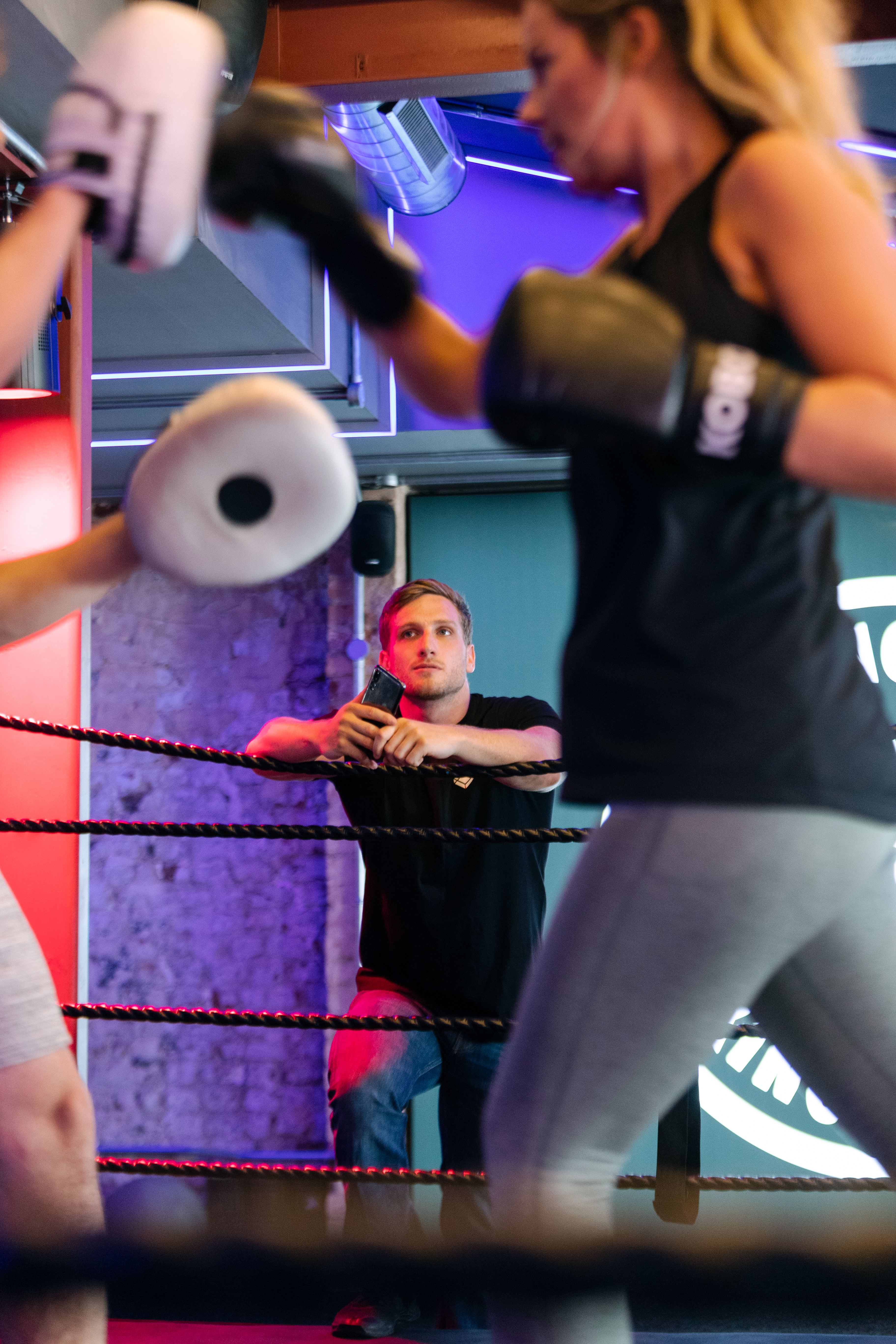 Male engineer monitors boxing performance through athletic devices. Female boxer trains.