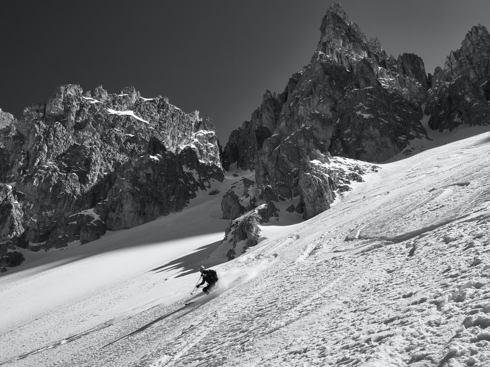 person riding on snow ski in grayscale photography