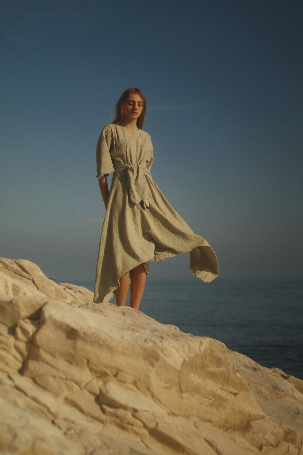 woman in brown dress standing on brown rock formation during daytime