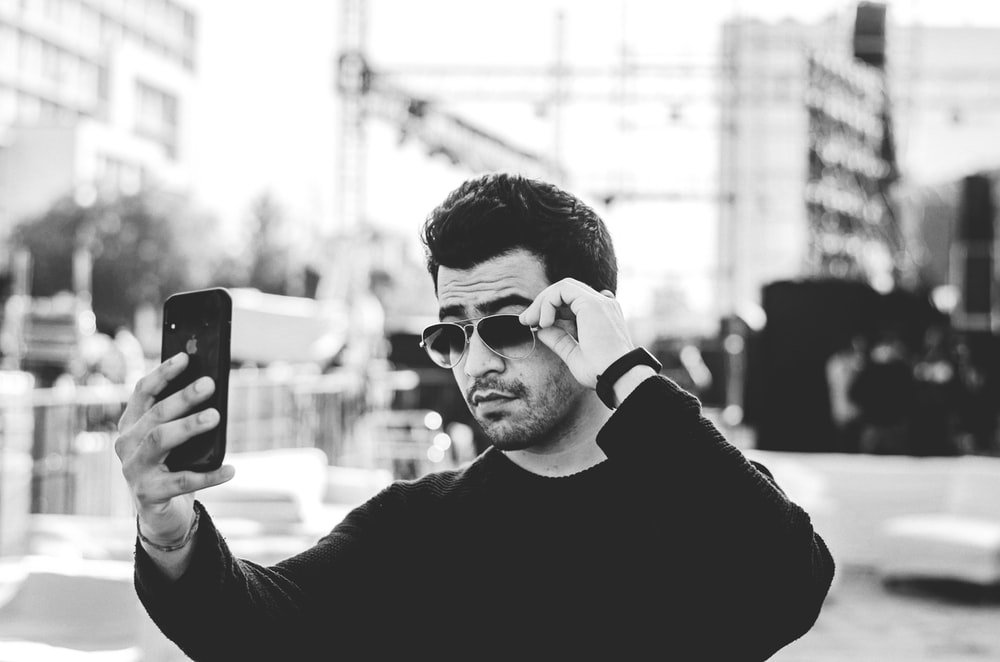 man in black long sleeve shirt holding iphone