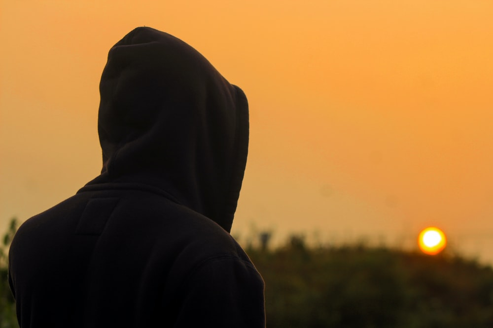 person in black hoodie standing during daytime