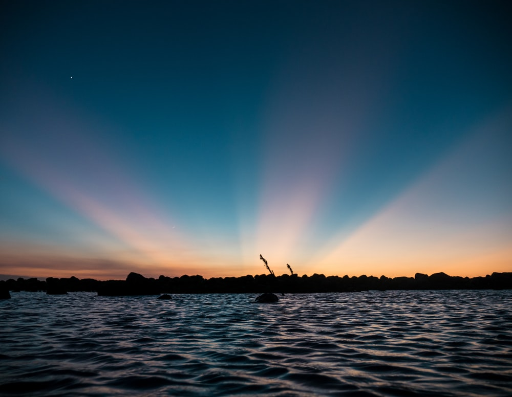 body of water under blue sky during night time