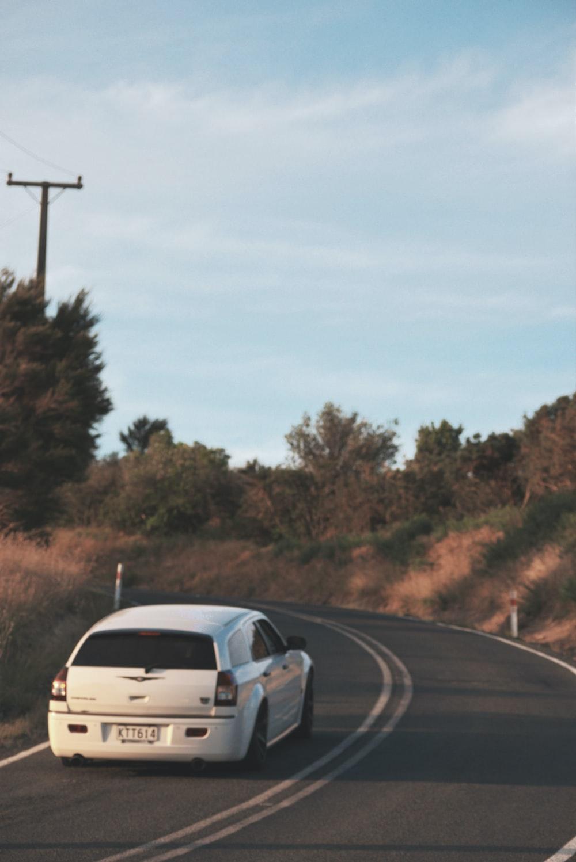 white sedan on road during daytime