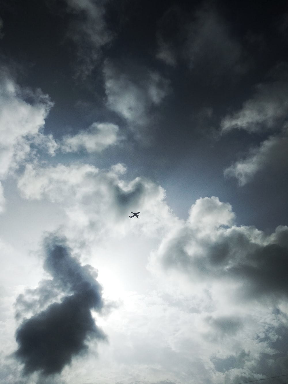 airplane flying under white clouds during daytime