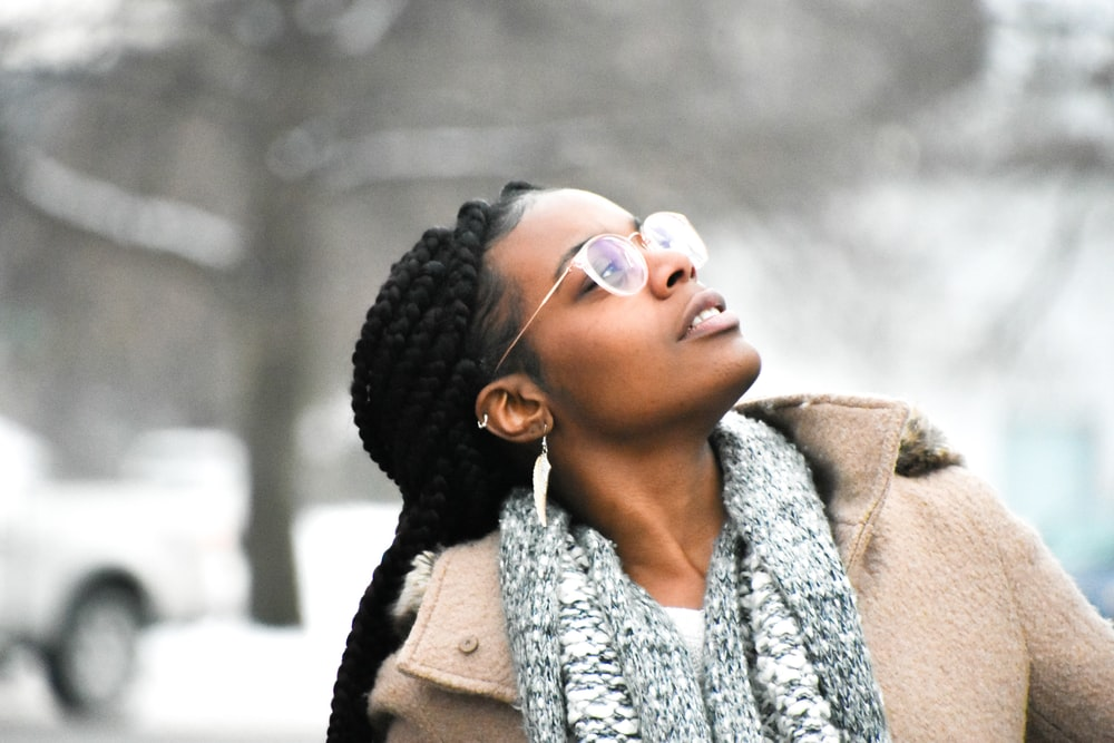 woman in brown coat wearing white and black scarf