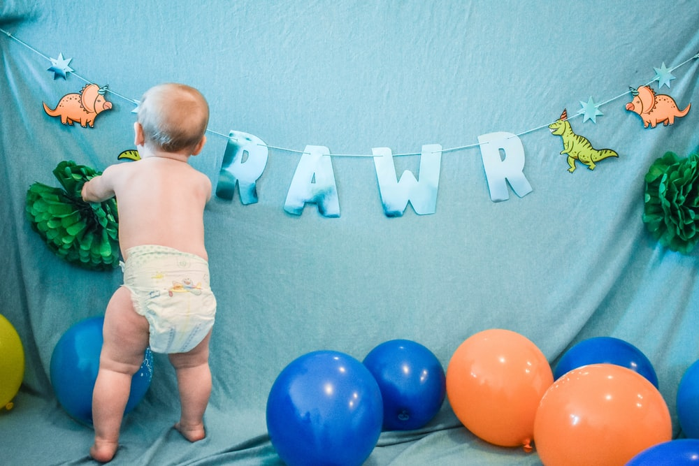 baby in white diaper standing beside blue and red balloons