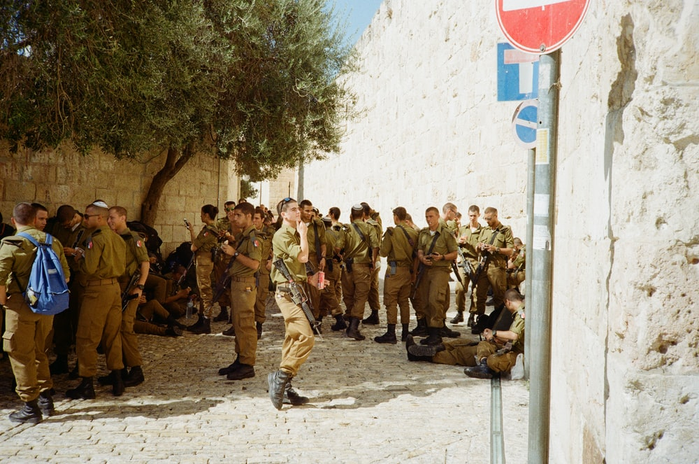 soldiers in green and brown camouflage uniform standing on white sand during daytime