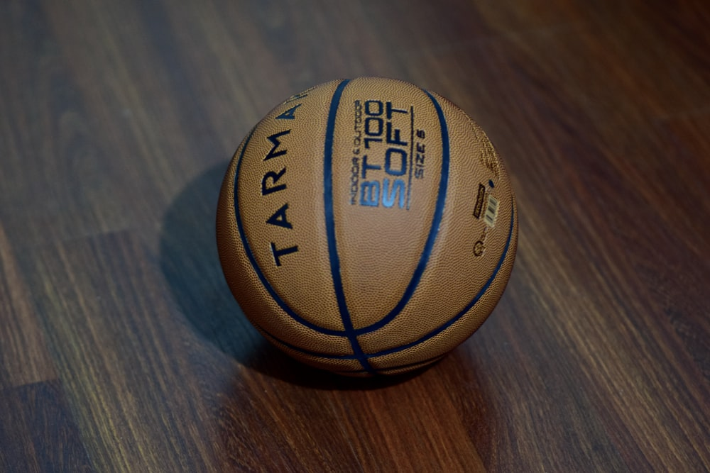 brown and black basketball on brown wooden table