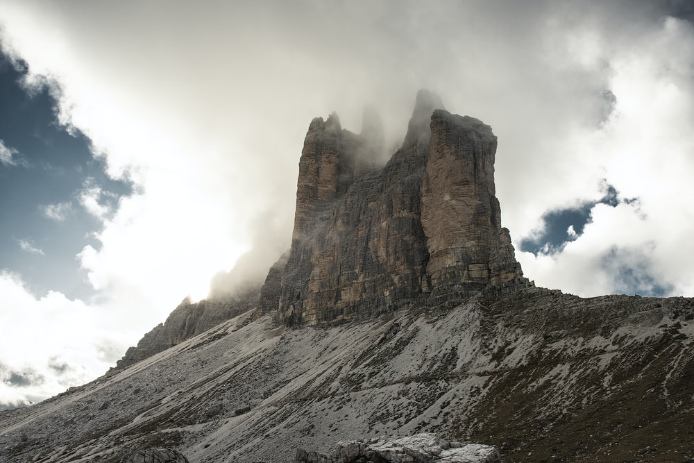 brown rocky mountain under white clouds during daytime