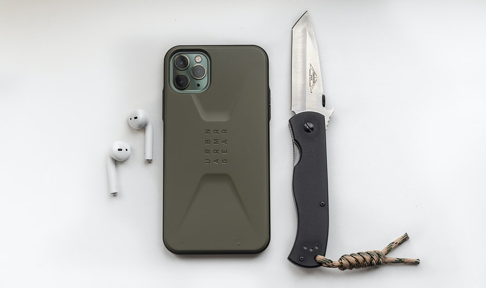 green iphone 5 c beside black and brown knife