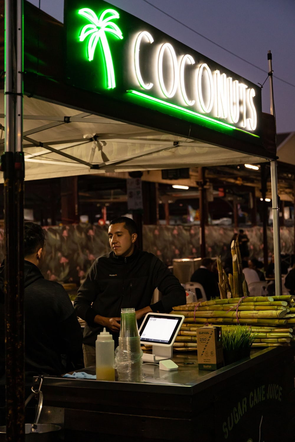 man in black jacket standing in front of food stall