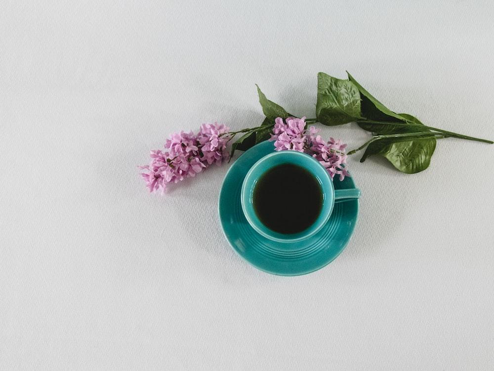 pink flower beside blue ceramic mug