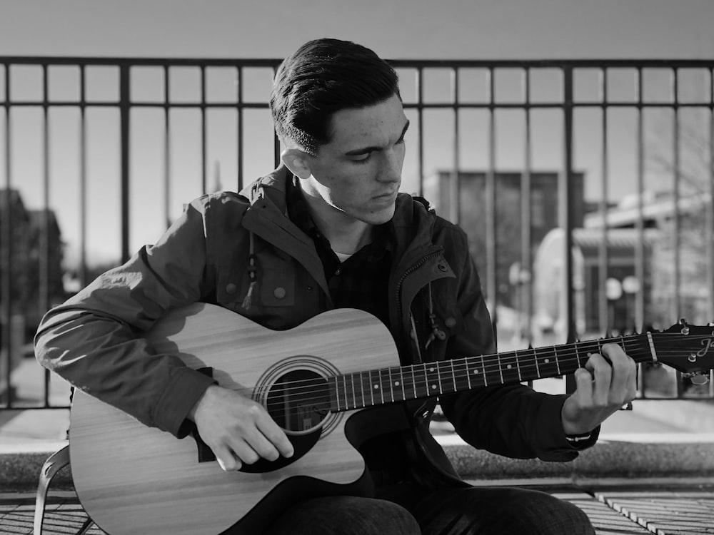 man in black jacket playing acoustic guitar