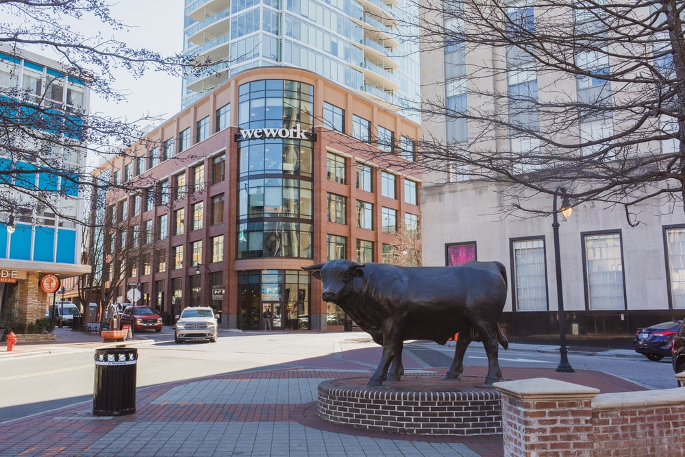 black cow statue on street during daytime