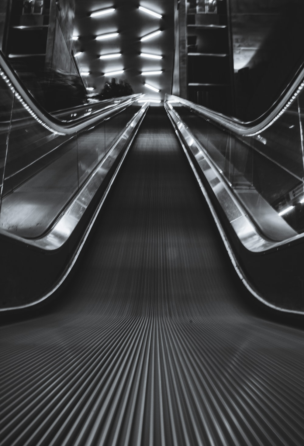 black and silver escalator in a tunnel