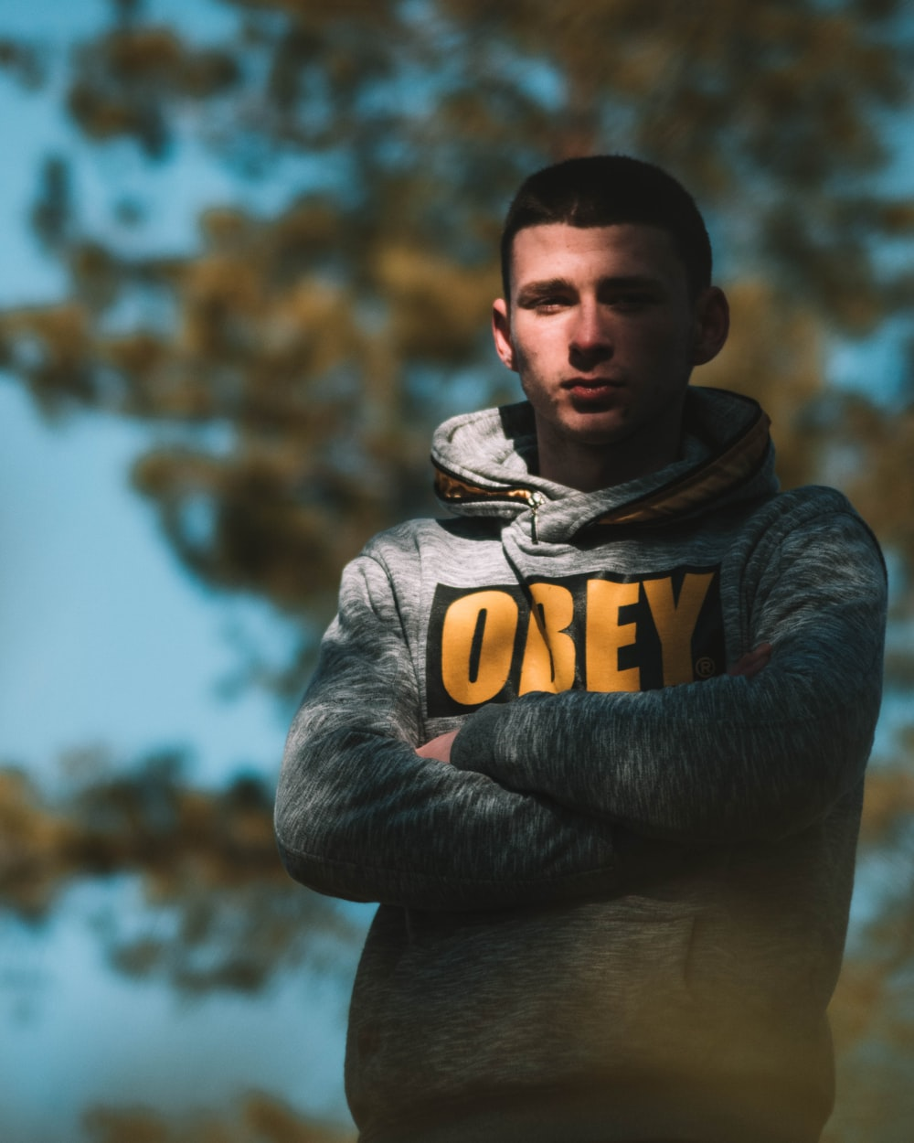 man in gray and yellow hoodie standing near brown trees during daytime