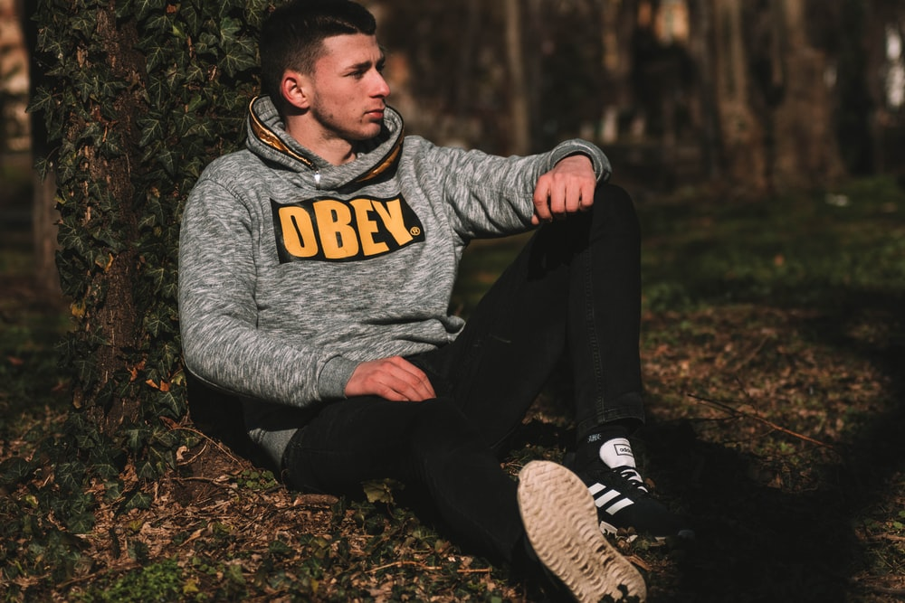 man in gray hoodie and black pants sitting on ground