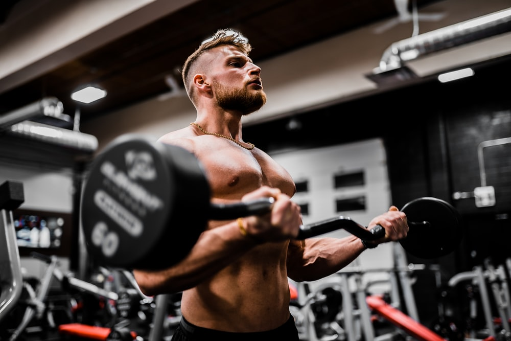 topless man in black shorts carrying black dumbbell