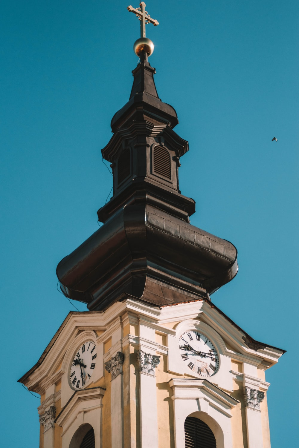 brown concrete tower with clock under blue sky during daytime