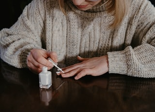 woman in gray sweater holding cigarette stick