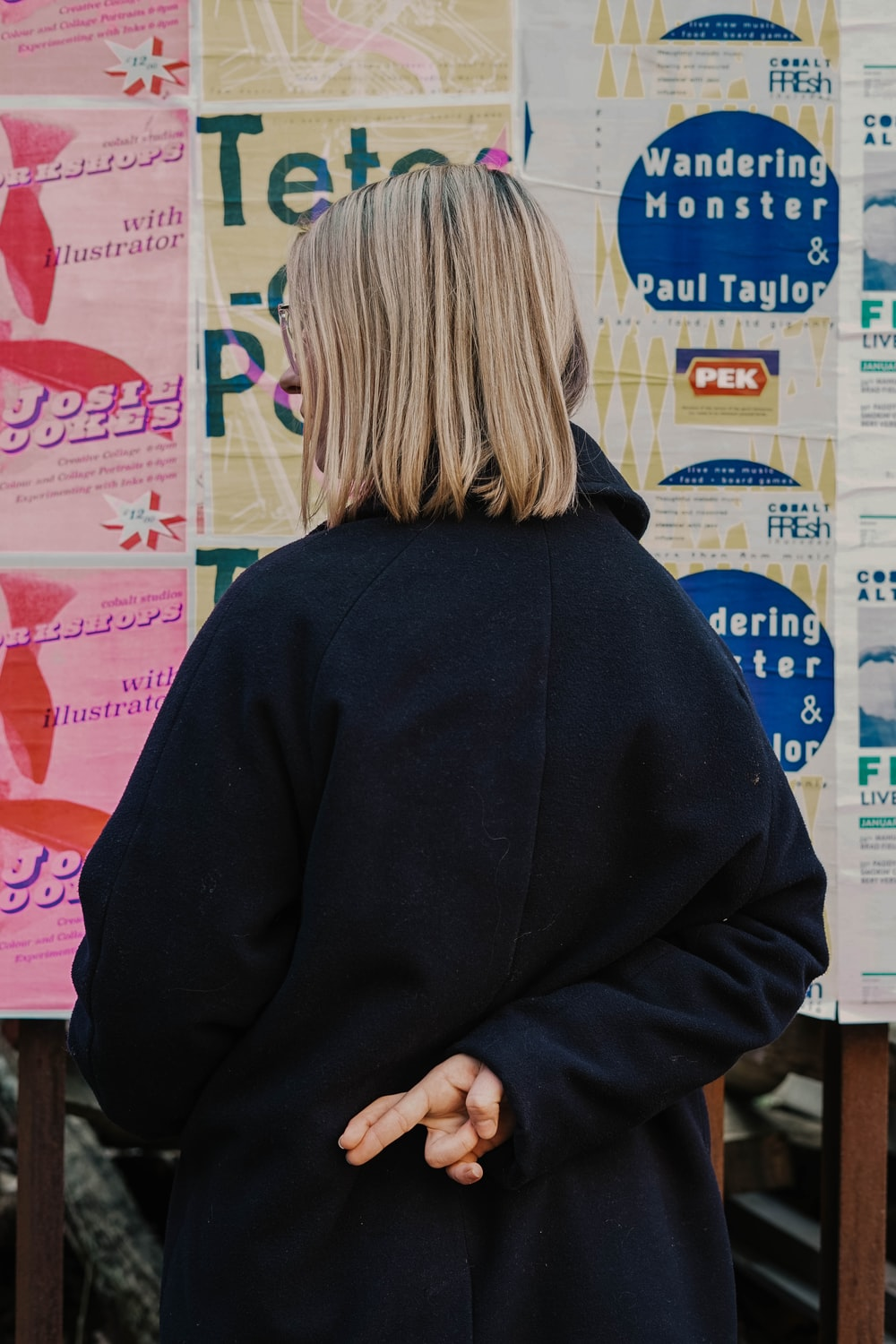 woman in blue hoodie standing in front of white and red kanji text signage
