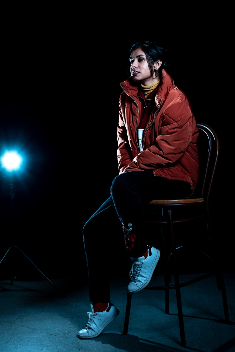 man in red jacket sitting on chair