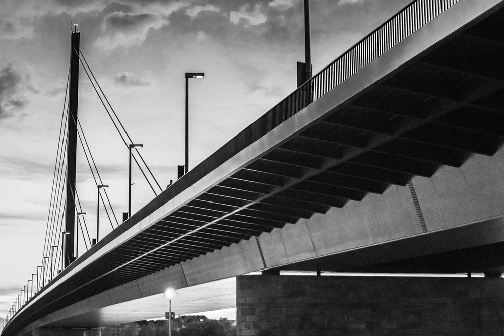 grayscale photo of bridge under cloudy sky
