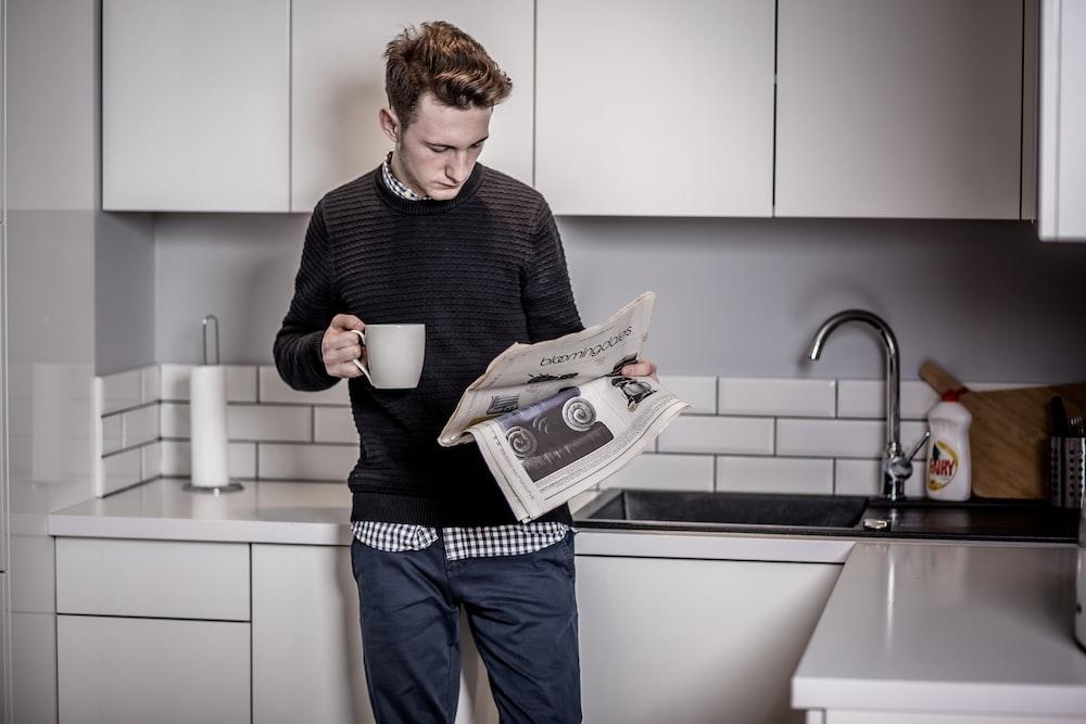 man in black sweater holding white ceramic mug