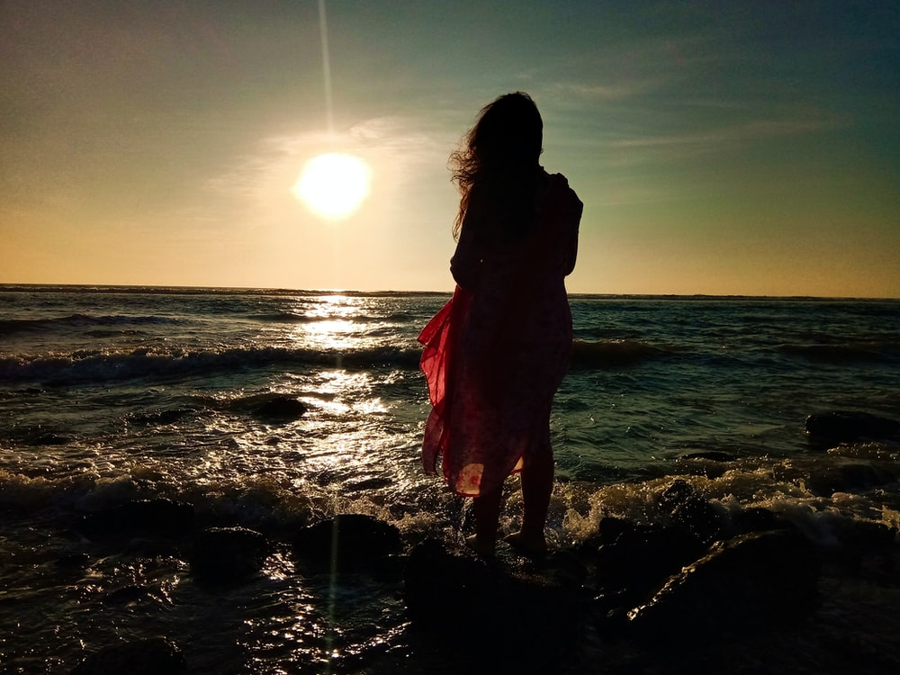woman in red dress standing on water during sunset