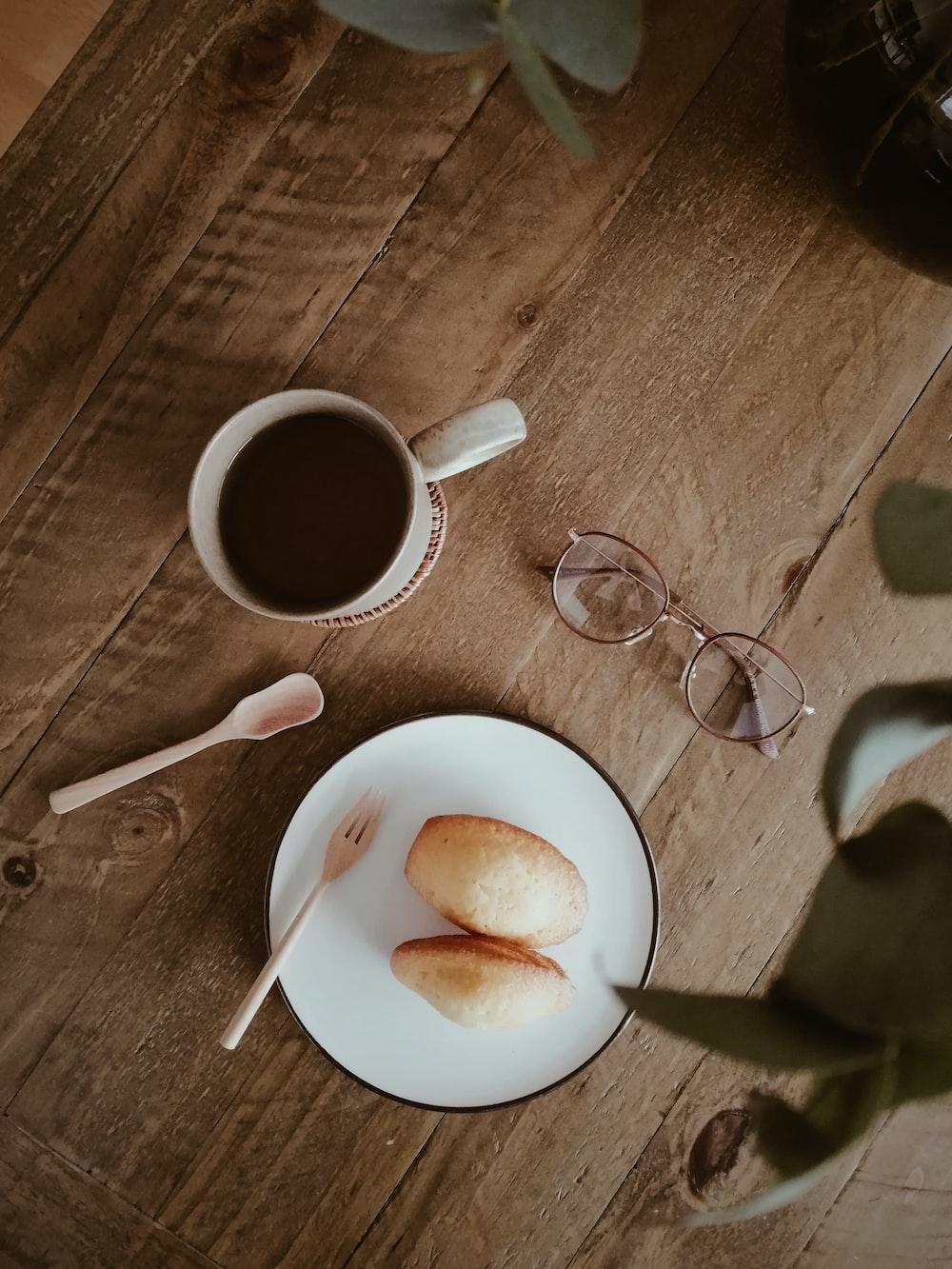 white ceramic mug beside stainless steel spoon on brown wooden table