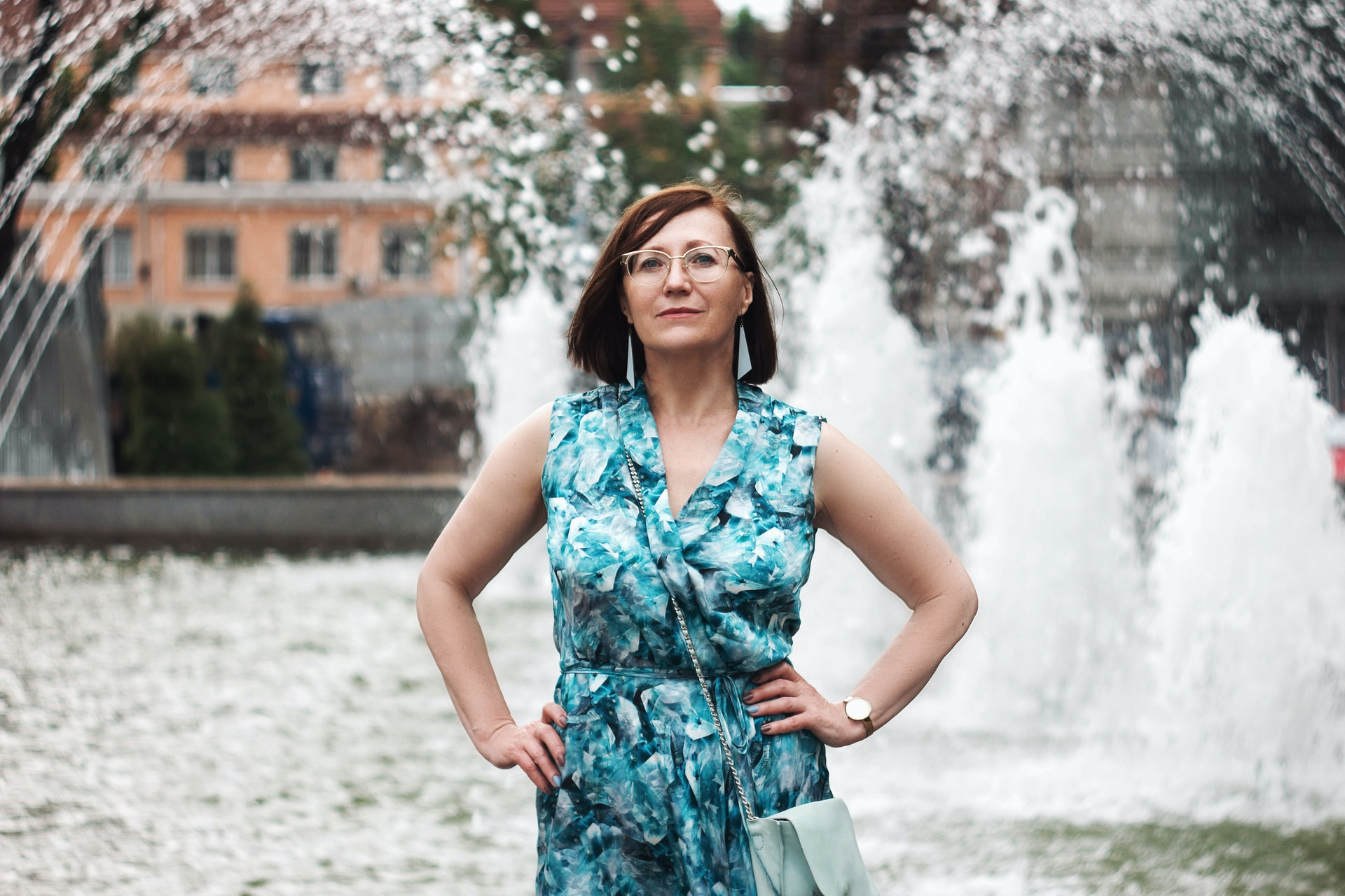 woman in blue and white floral sleeveless dress standing on snow covered ground during daytime