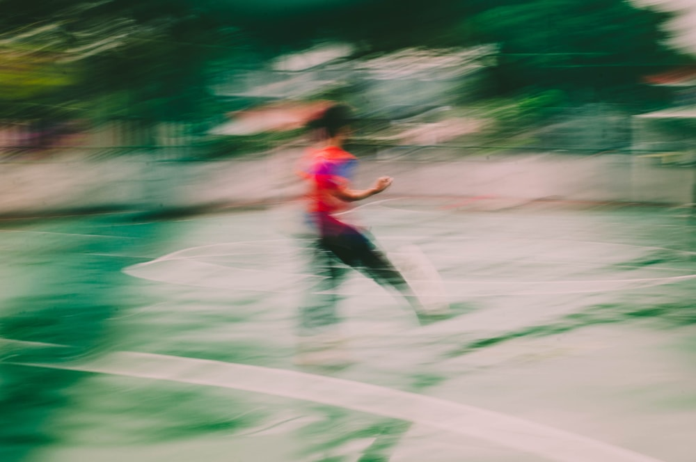 man in red shirt and black pants running on road during daytime
