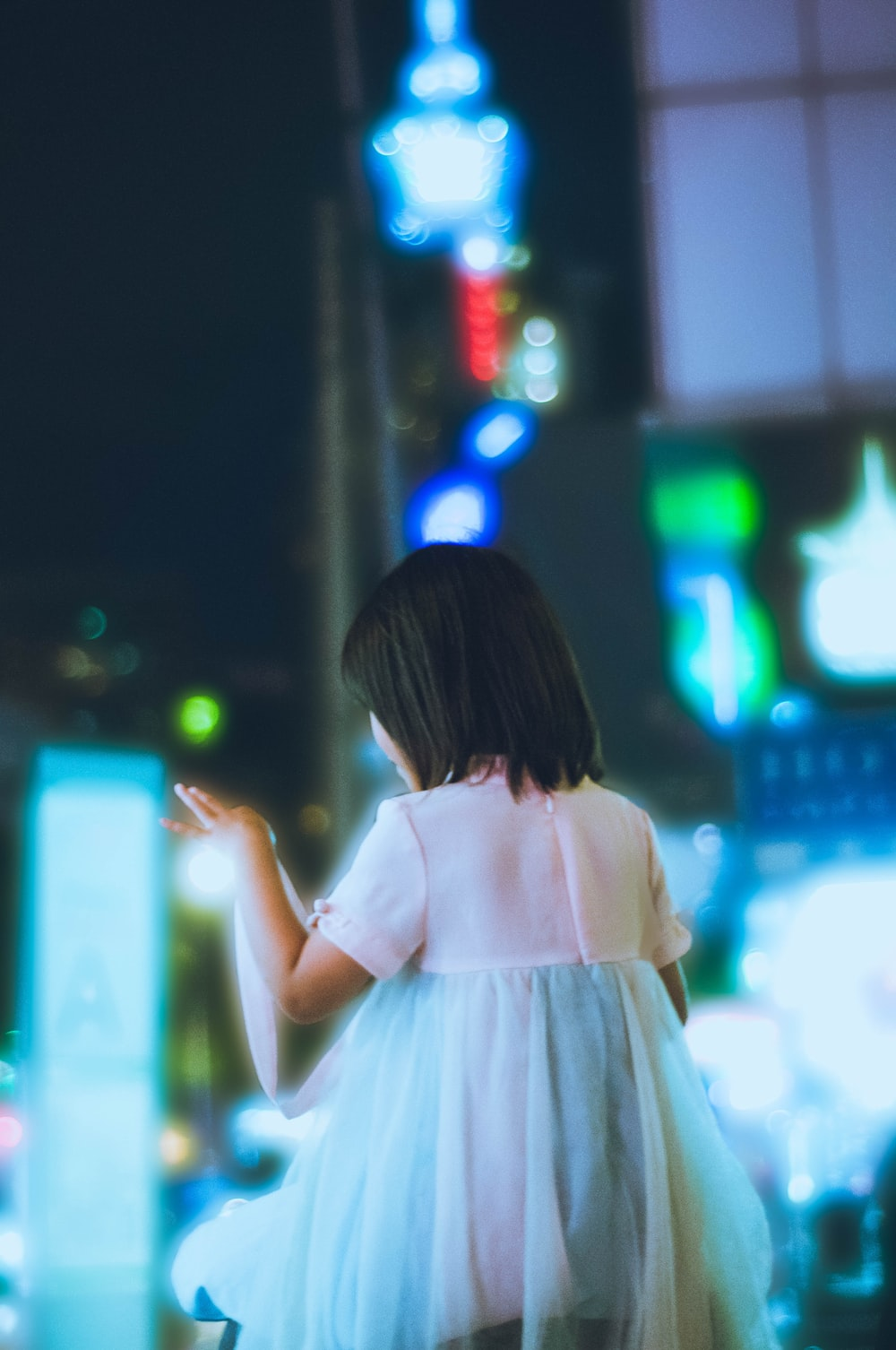 girl in white dress standing on street during night time