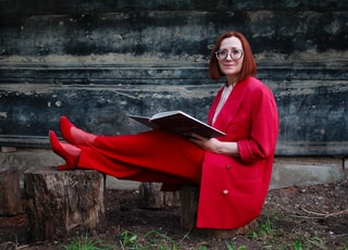 woman in red robe sitting on brown wooden bench
