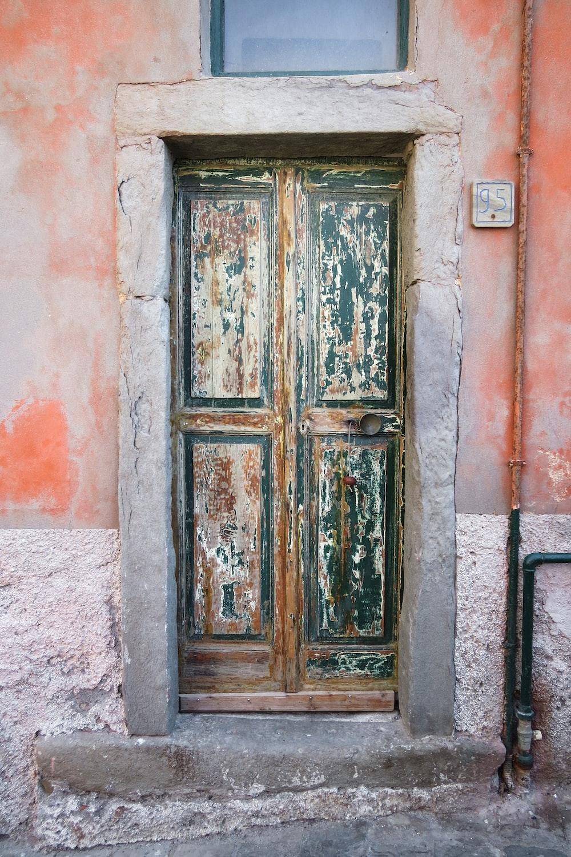 brown wooden door on red concrete wall
