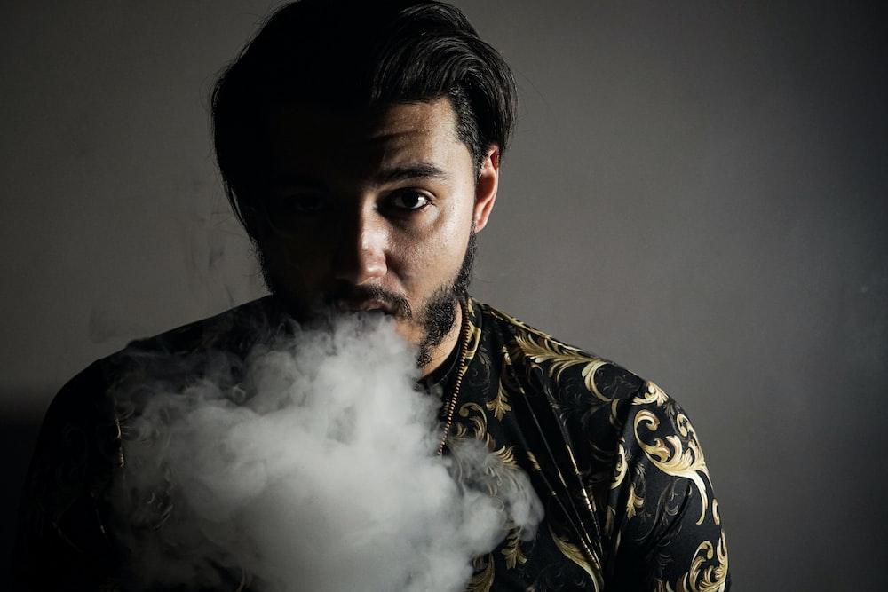 man in black and yellow floral shirt smoking