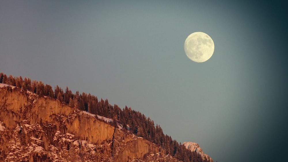 brown rocky mountain under full moon