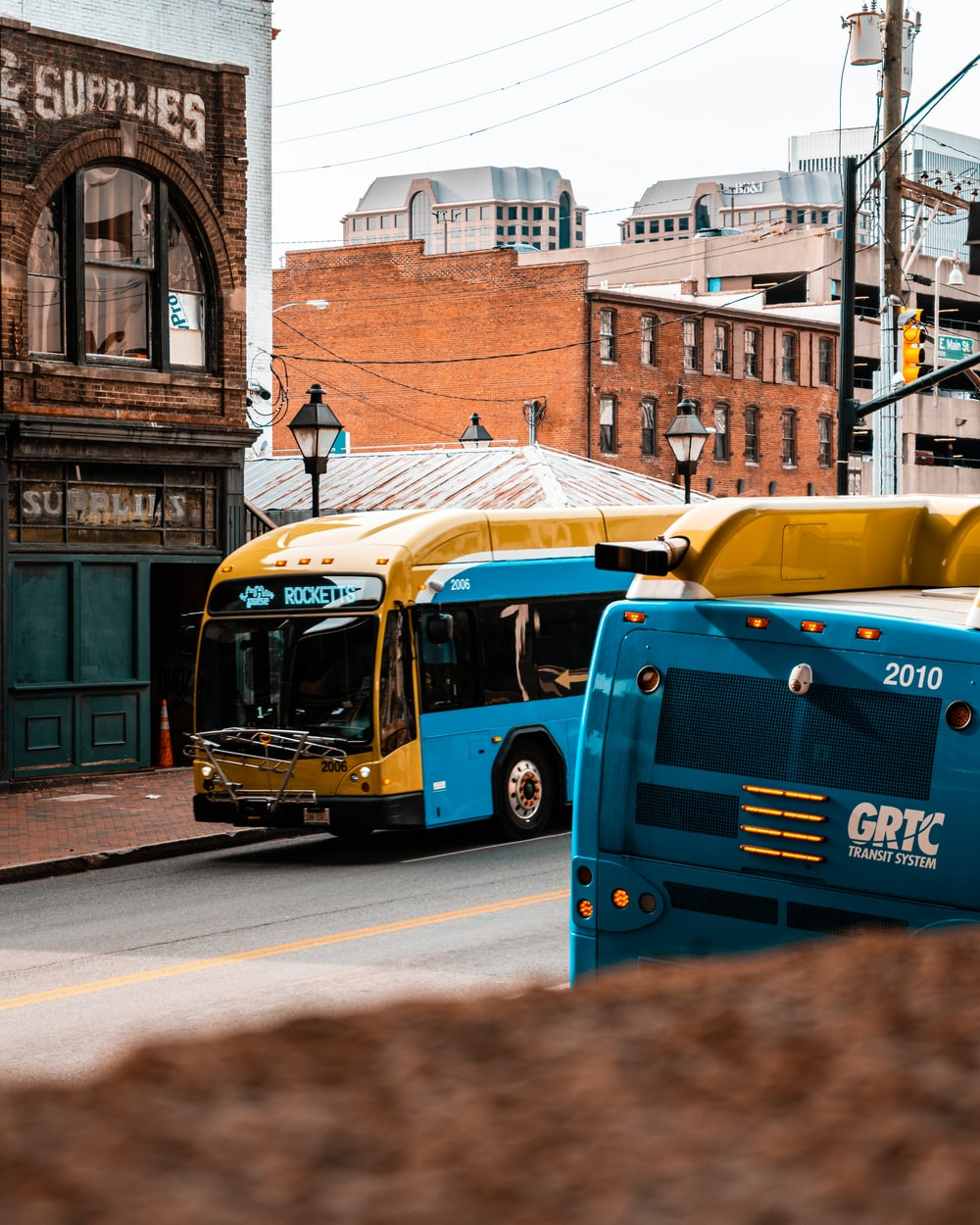 blue and yellow bus on road during daytime