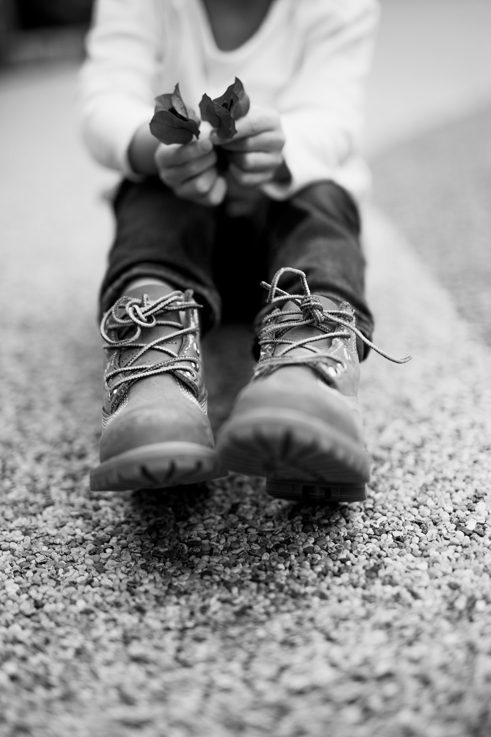 grayscale photo of person wearing hiking shoes