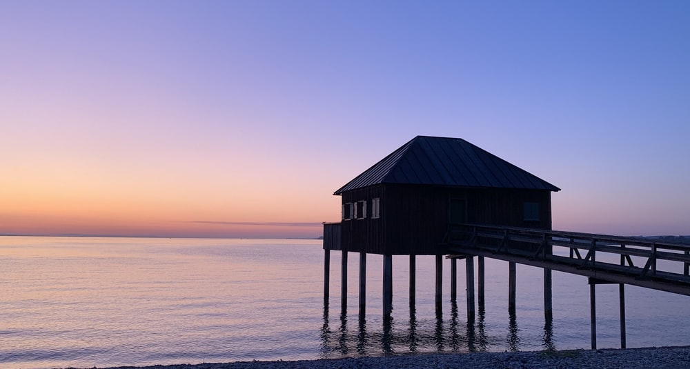 brown wooden house on sea during sunset