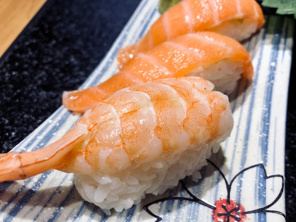 orange and white sushi on white plastic container